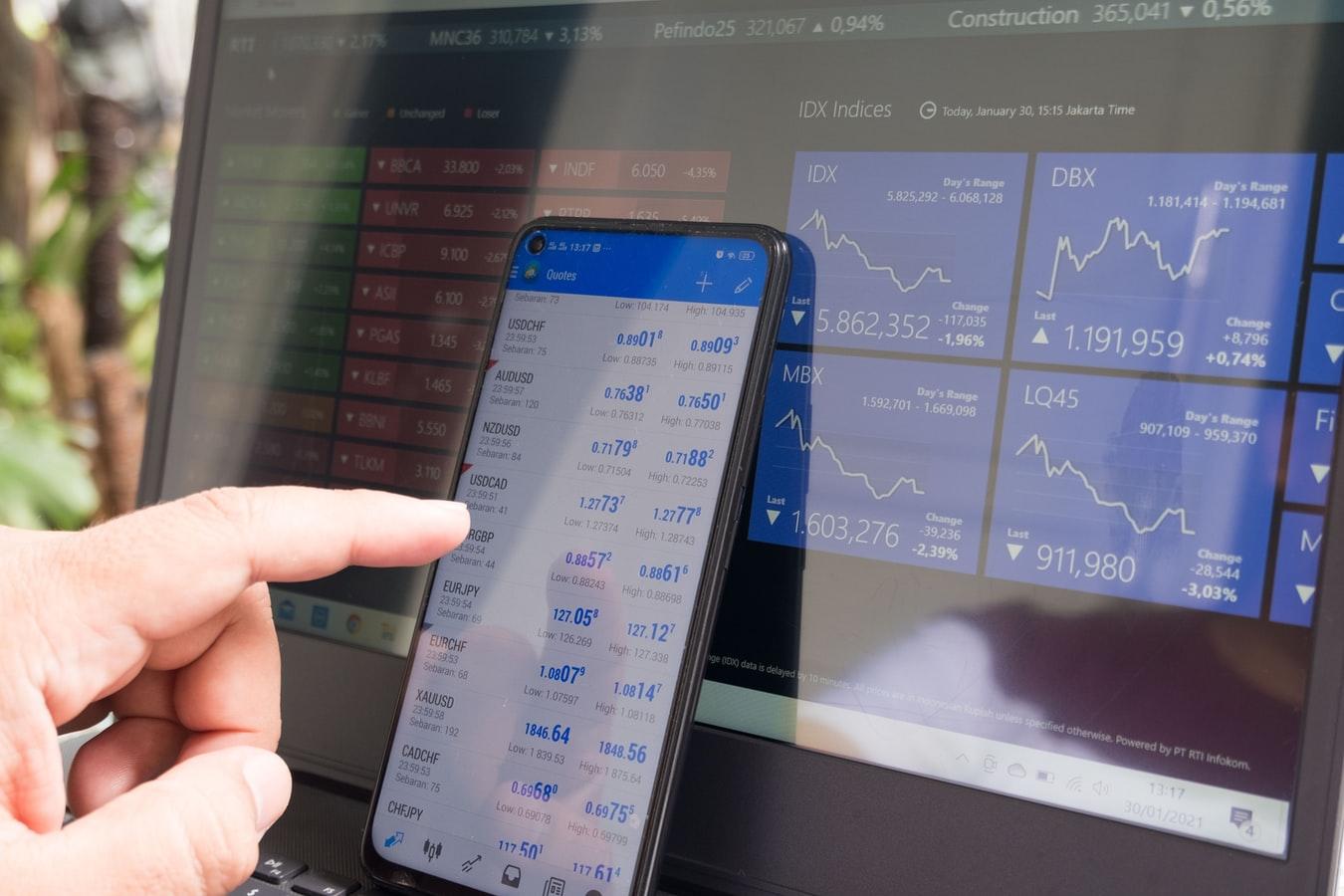 imagem - mão mexendo em um smartphone em frente a uma tela de computador acompanhando resultados de investimentos