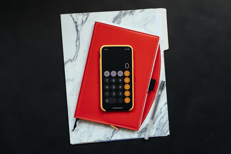 imagem - iphone com o aplicativo da calculadora aberto em cima de um caderno vermelho