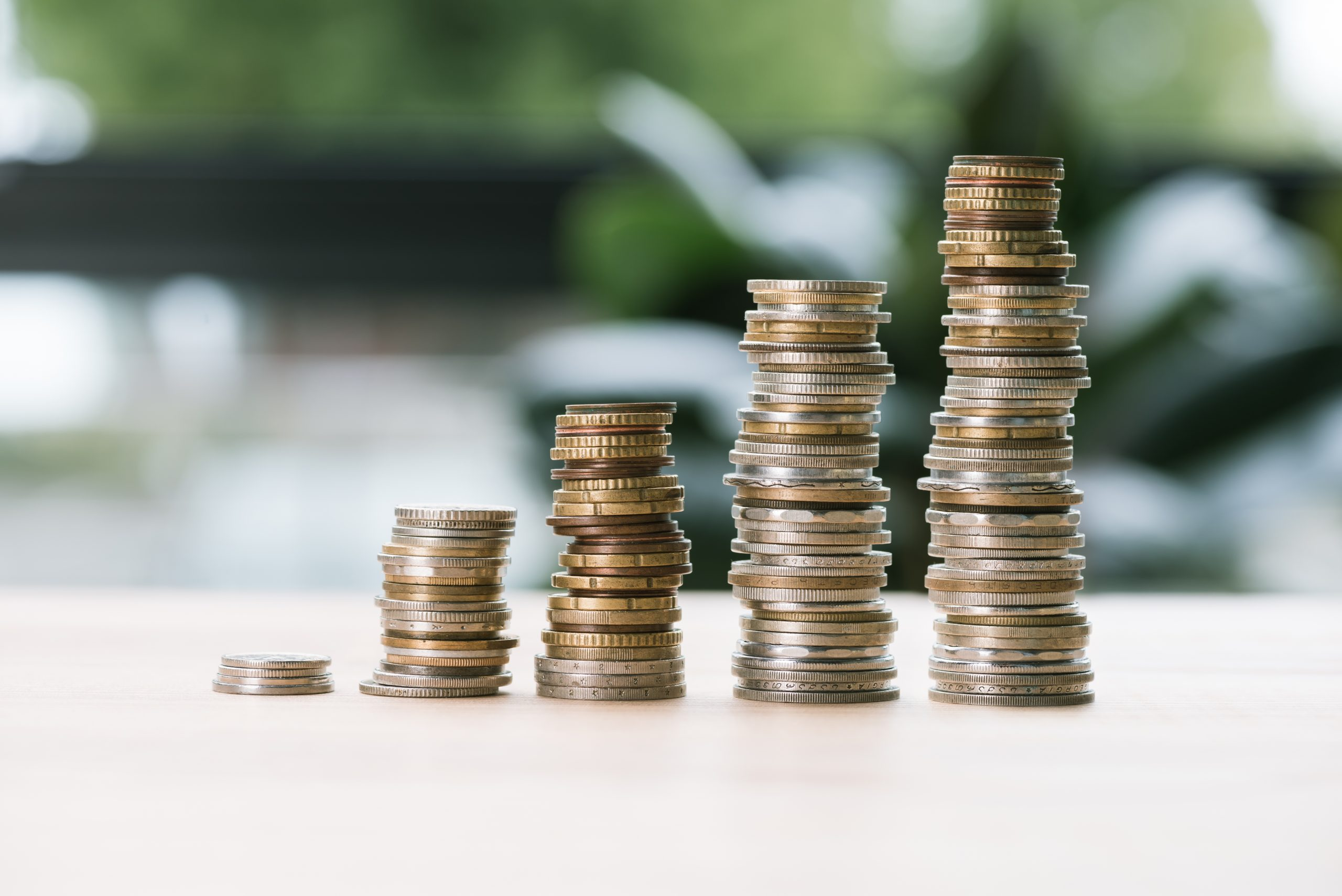 fundamentos da construção de riqueza com investimento a longo prazo - imagem: foco seletivo em montes baixos e altos de moedas em uma mesa