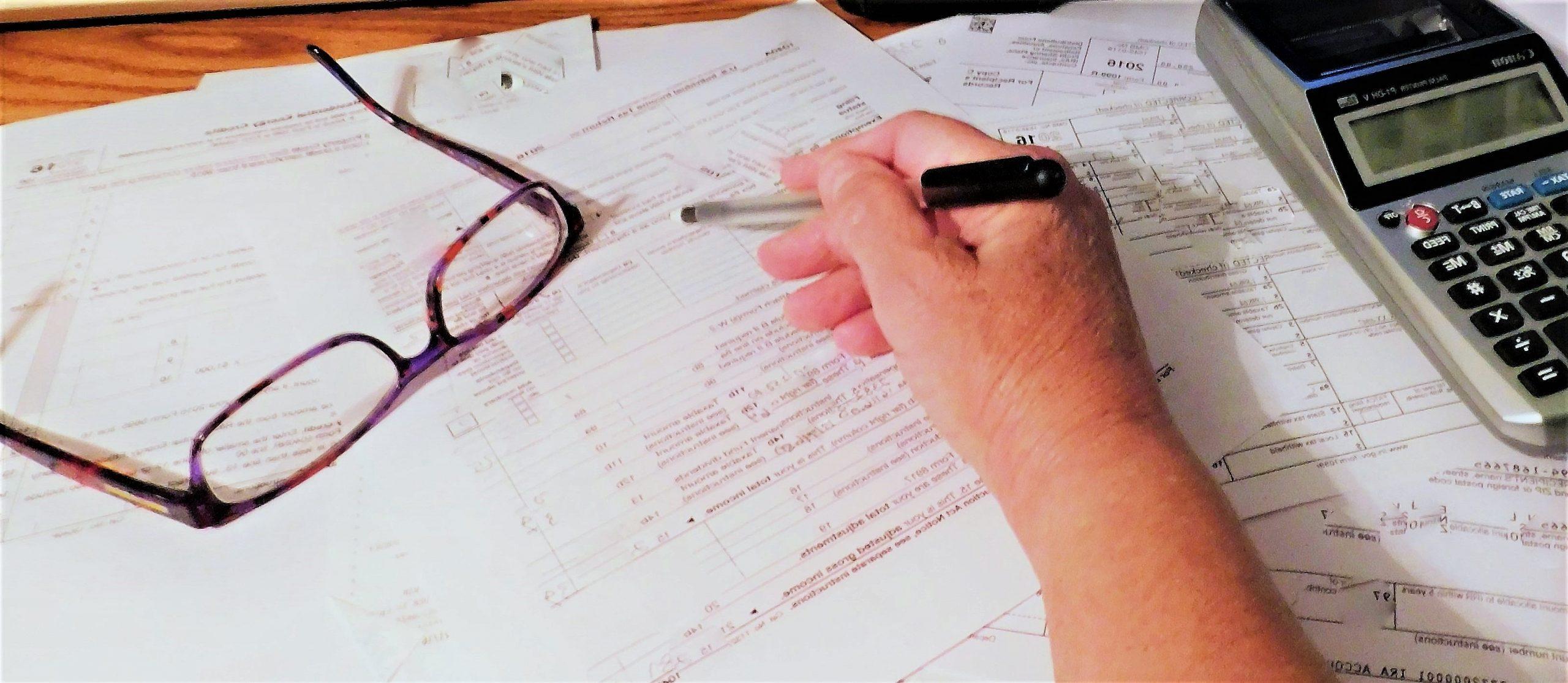 Imposto de renda de ETF - foto de uma mão segurando uma caneta fazendo cálculos de imposto sobre folhas de papel. Existem um óculos e uma calculadora em cima dos papéis.